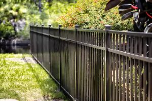 Angle view of black Wrought Iron Fence among trees in Orange County, California